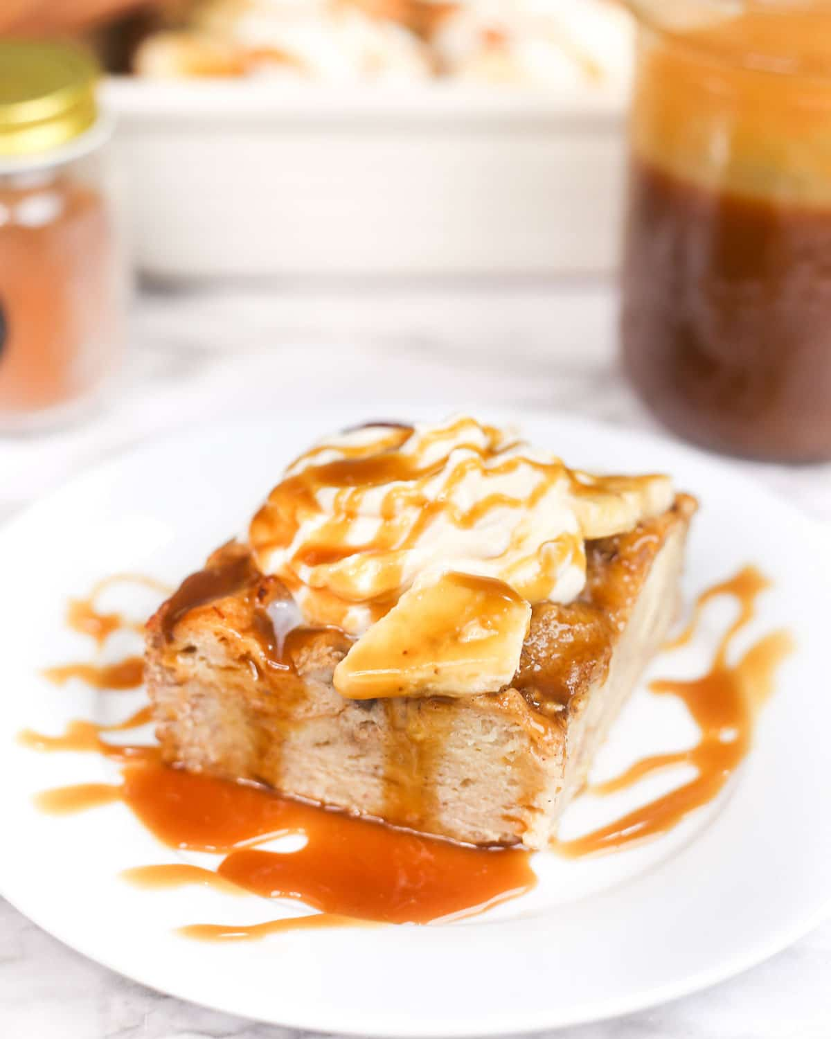 a plate of bread pudding served with banana slices, whipped cream, and caramel sauce.