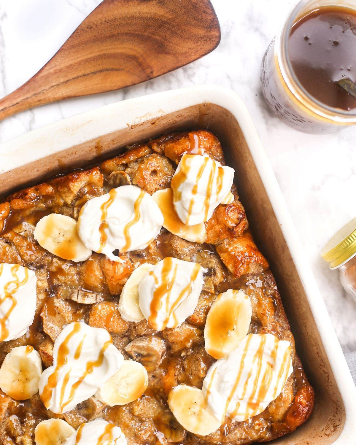 a casserole dish of banana bread pudding topped with whipped cream and caramel
