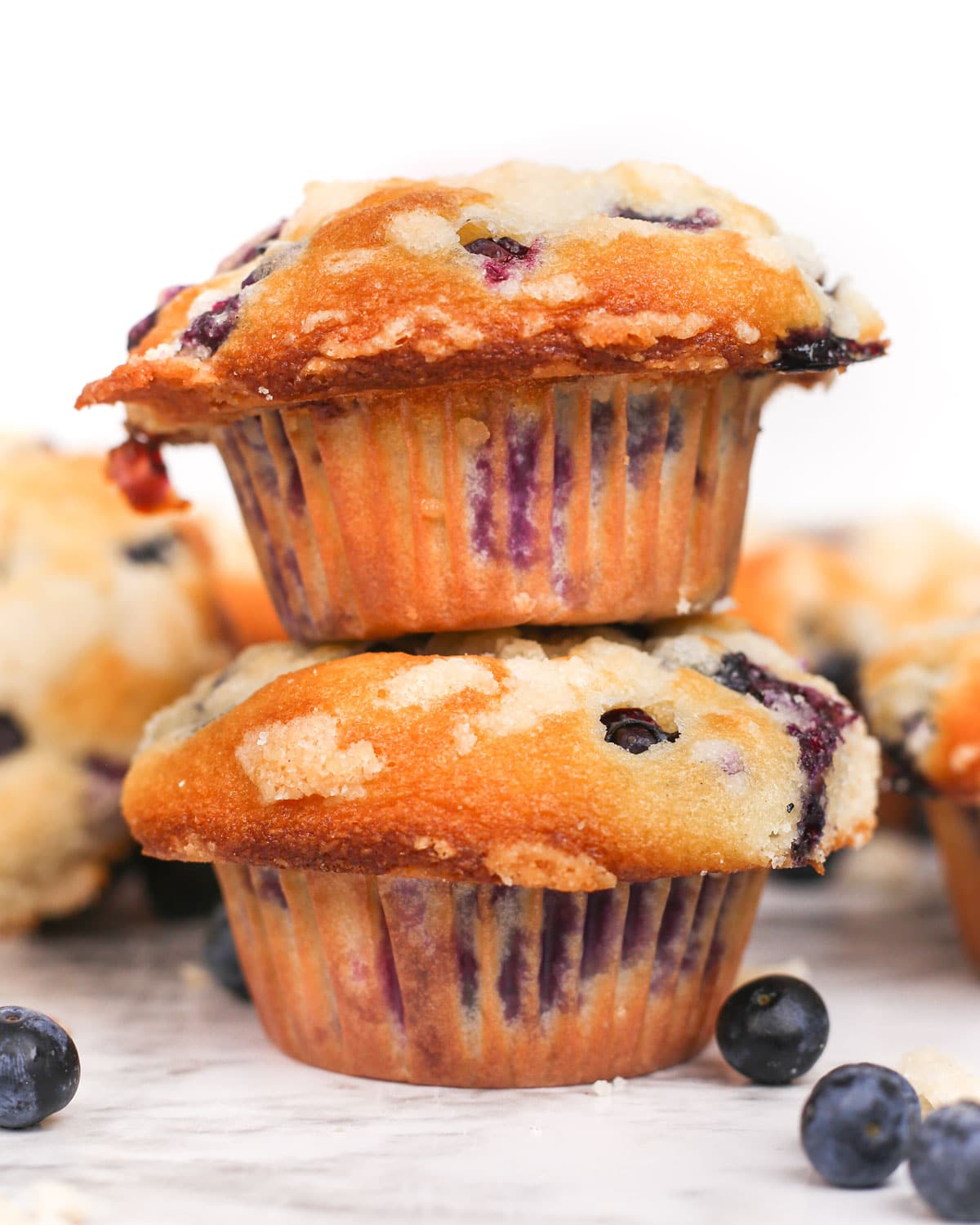 two blueberry streusel muffins stacked on top of each other