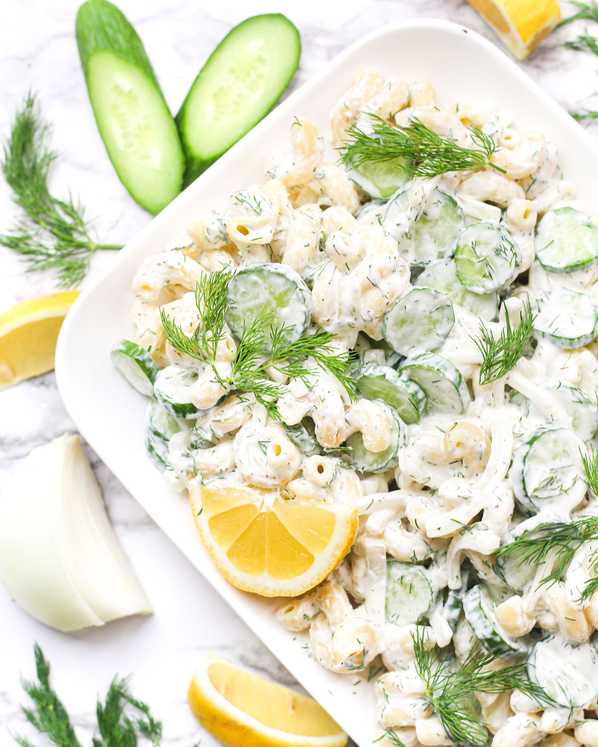 creamy cucumber pasta salad topped with fresh dill and lemon