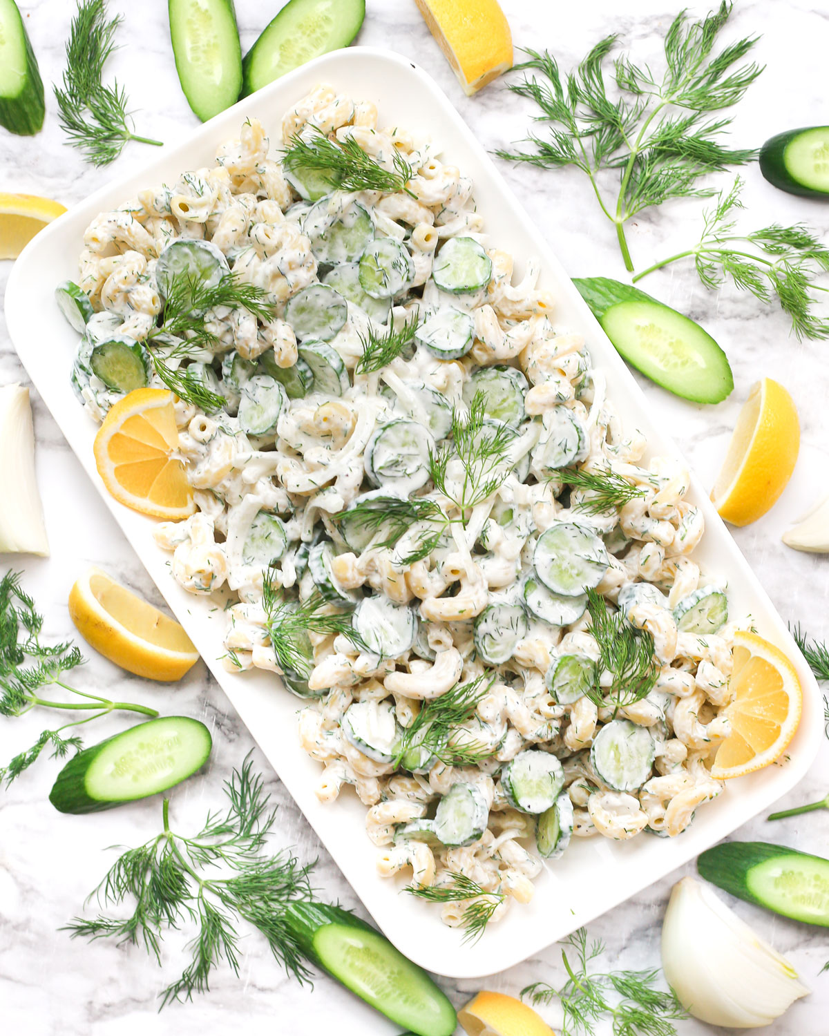 a platter of creamy cucumber pasta salad topped with fresh lemon wedges and dill