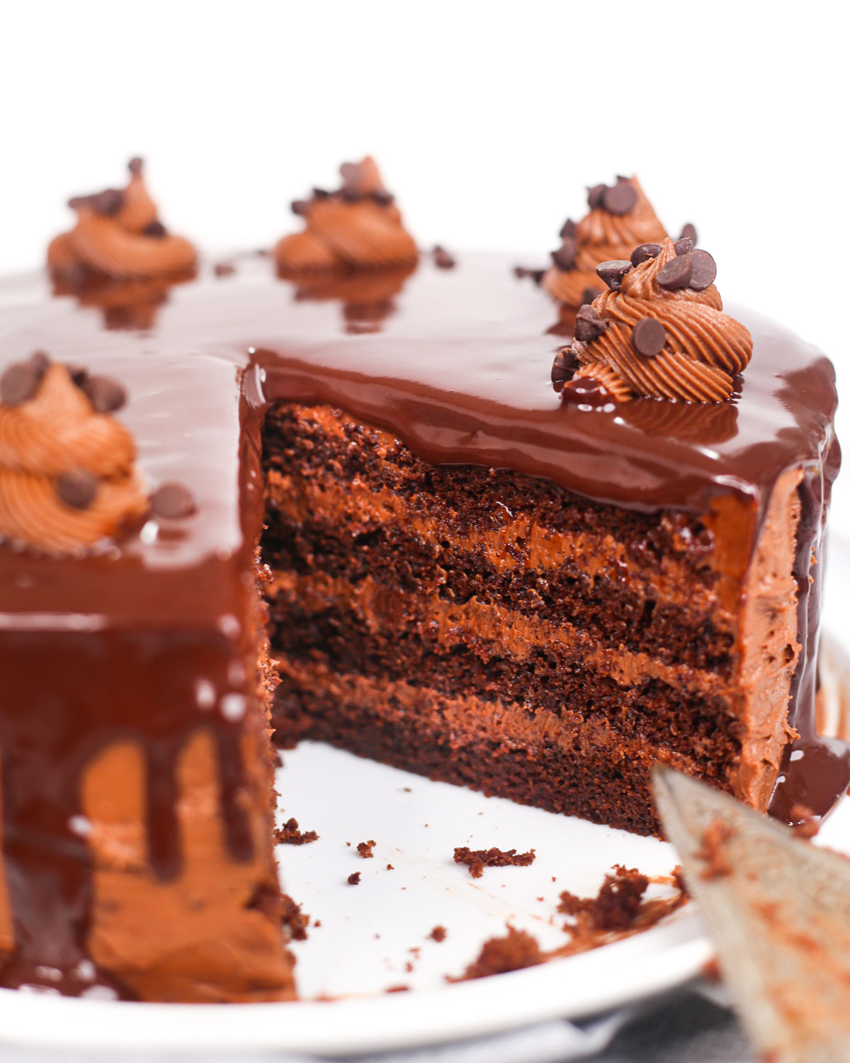 death by chocolate cake with a piece cut from it revealing the layers of buttercream inside