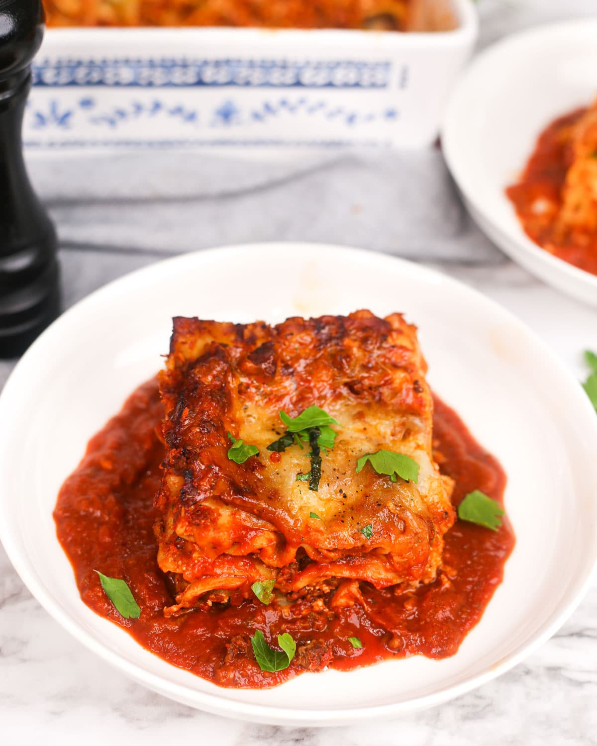 a slice of lasagna on a plate with tomato sauce