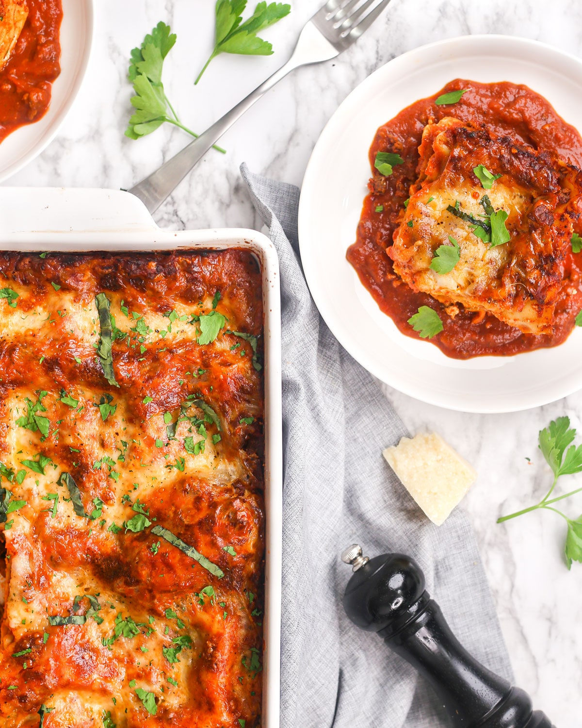a casserole dish of lasagna with a slice of lasagna on a plate