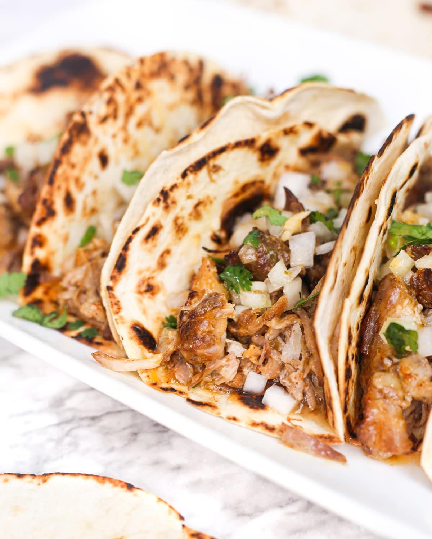 closeup of a taco filled with pork carnitas, onion, and cilantro.