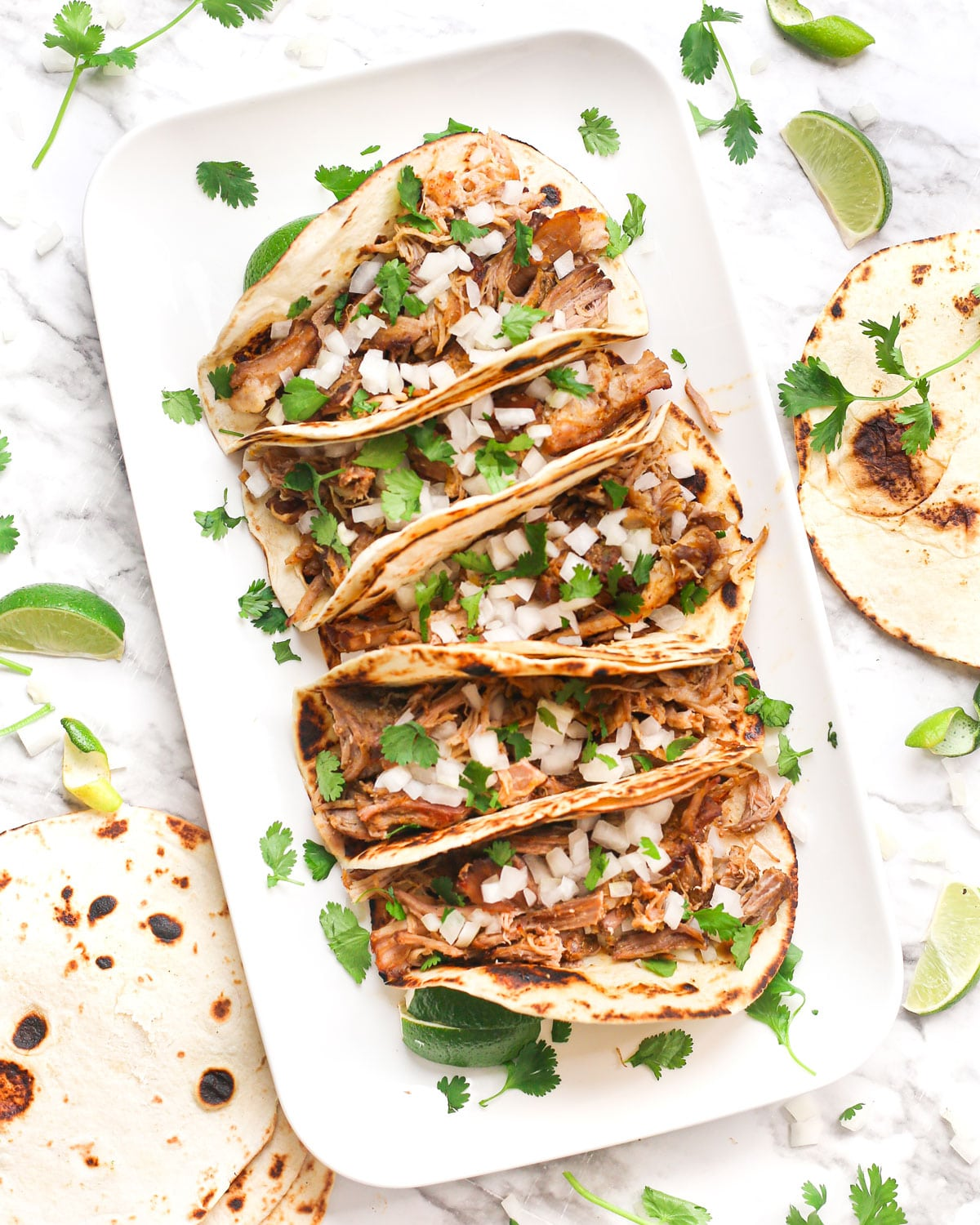 a platter of slow cooker pork carnitas in tortillas topped with fresh onion and cilantro