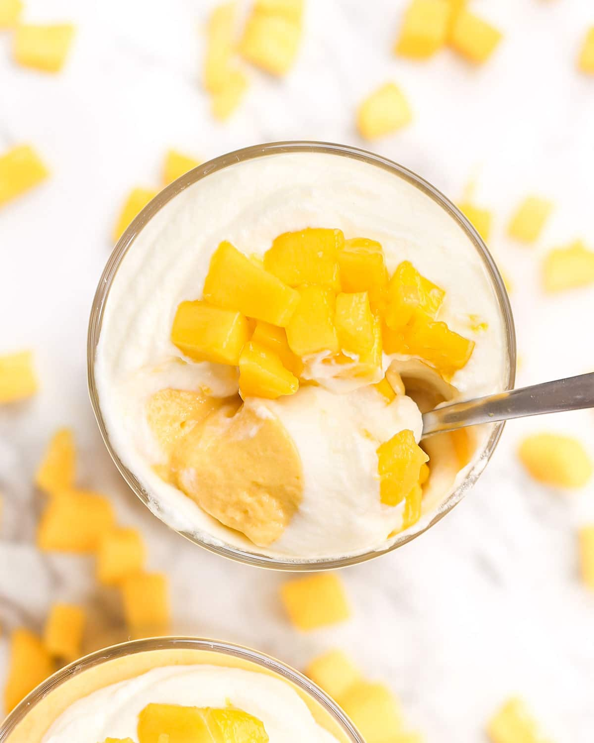 a spoon scooping mango mousse topped with whipped cream from a glass