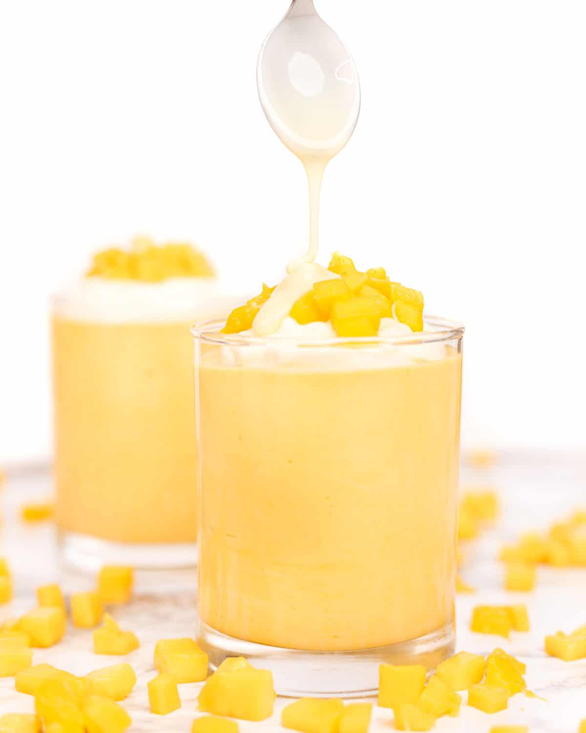 a spoon drizzling condensed milk over a glass of mango mousse