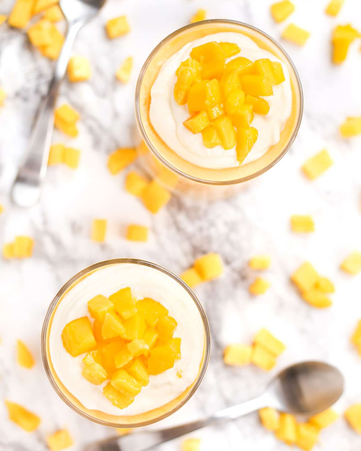 overhead photo of mango mousse topped with whipped cream and diced mango