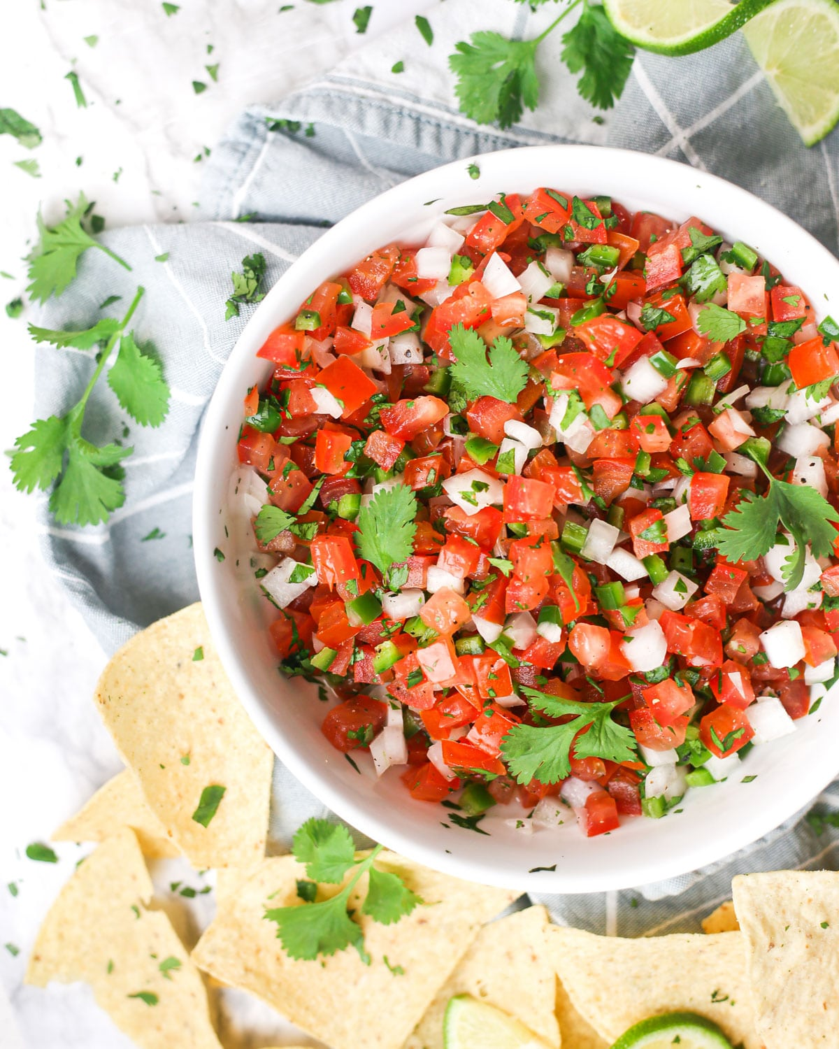 a bowl of pico de gallo surrounded by chips