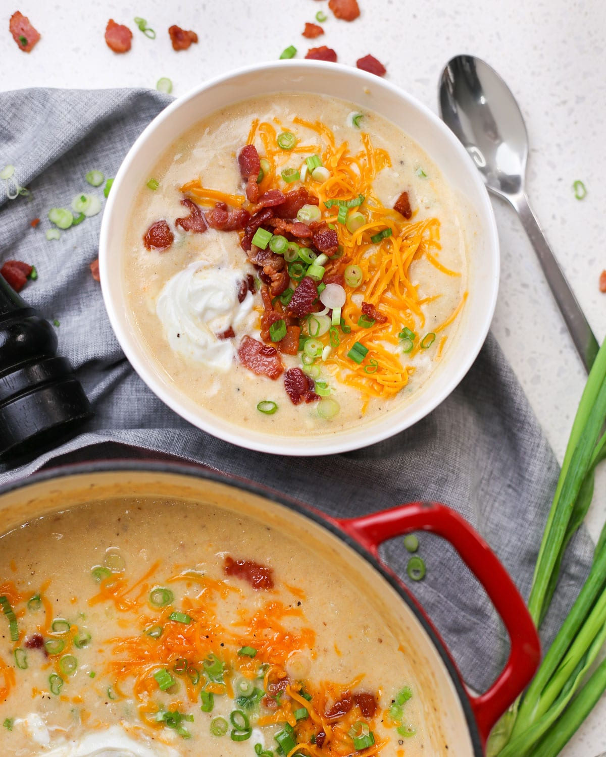 a bowl of baked potato soup topped with bacon, sour cream, green onion, and cheddar cheese