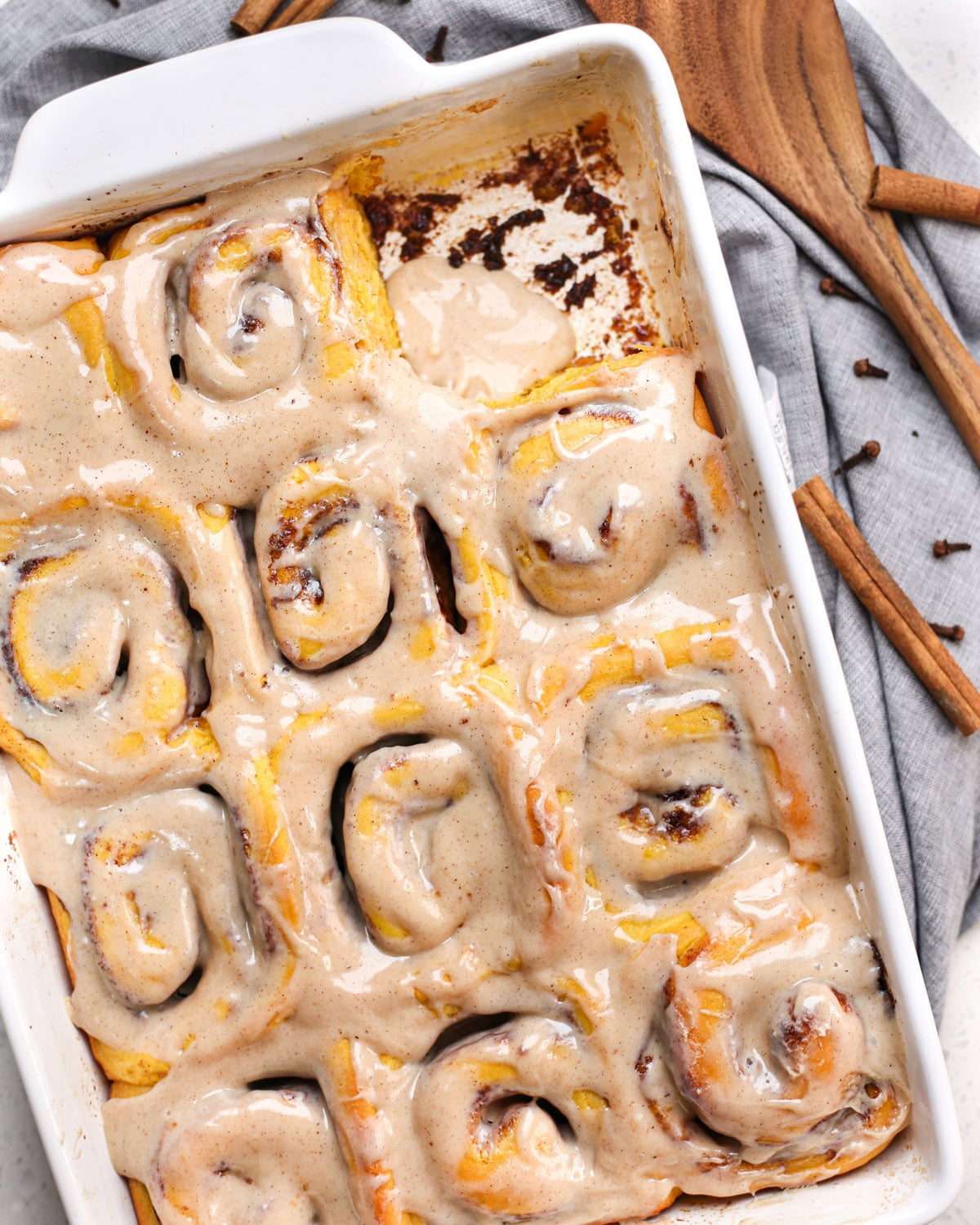 Pumpkin Spice Cinnamon Rolls in a baking dish with one roll removed